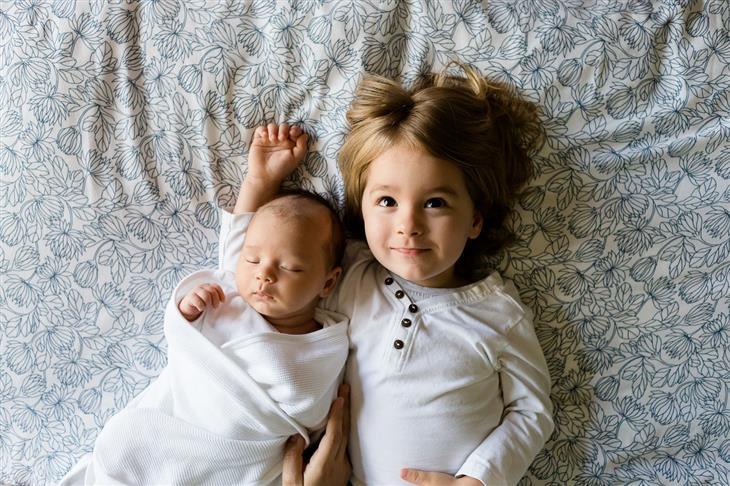 4 שלבי התפתחות הילד לפי ז'אן פיאז'ה: ילדה שוכבת על מיטה לצד תינוק
