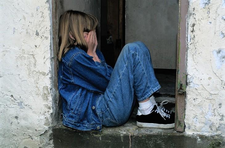 סיבות, סימנים ודרכי פעולה להתמודדות עם חרדות אצל ילדים: ילדה יושבת על מפתן הדלת ומכסה את פניה