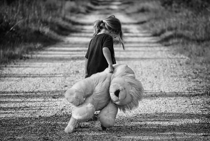 סיבות, סימנים ודרכי פעולה להתמודדות עם חרדות אצל ילדים: ילדה הולכת ומחזיקה בובת דובי גדולה