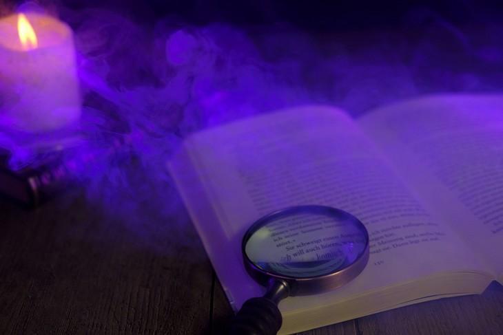 סיבות, סימנים ודרכי פעולה להתמודדות עם חרדות אצל ילדים: ספר פתוח ועליו מונחת זכוכית מגדלת, ברקע נר והתמונה אפופה בעשן