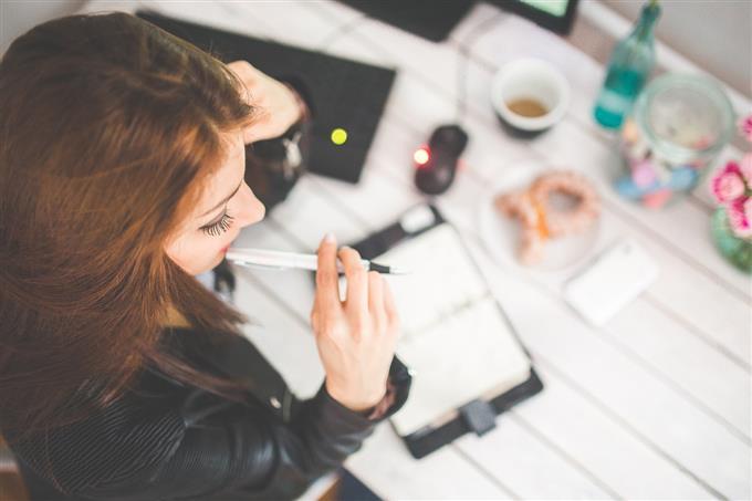 בחן את עצמך: אישה יושבת מול מחברת עם עט בפה