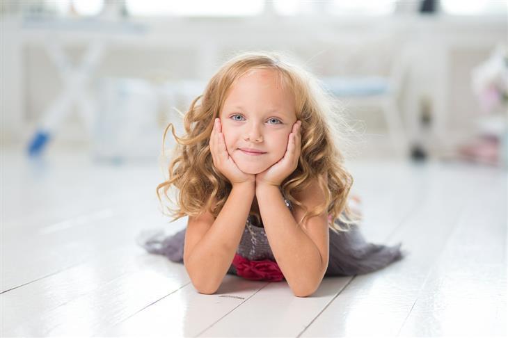 4 שלבי התפתחות הילד לפי ז'אן פיאז'ה: ילדה שוכבת על רצפה ומסתכלת למצלמה