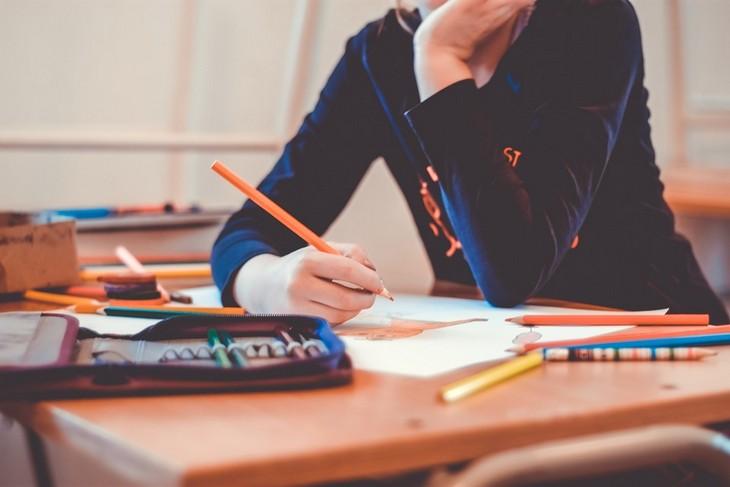 סיבות, סימנים ודרכי פעולה להתמודדות עם חרדות אצל ילדים: ילדה יושבת ליד שולחן ומחזיקה עפרון