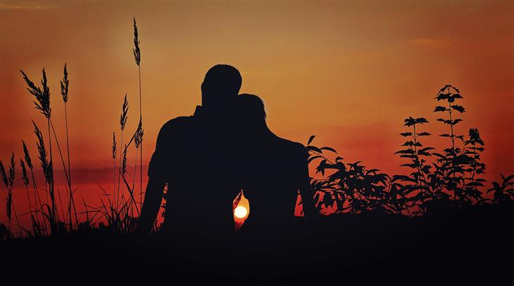 טיפים ליחסים ממומחי זוגיות: צללית של זוג בשדה מול שקיעה