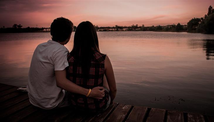 טיפים ליחסים ממומחי זוגיות: גבר ואישה יושבים על מזח בשעת בין ערביים