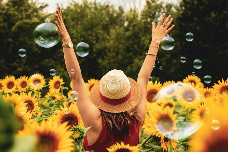 כלים לחיים מאושרים: אישה מרימה ידיים לאוויר בשמחה בתוך שדה פרחים ובועות סבון