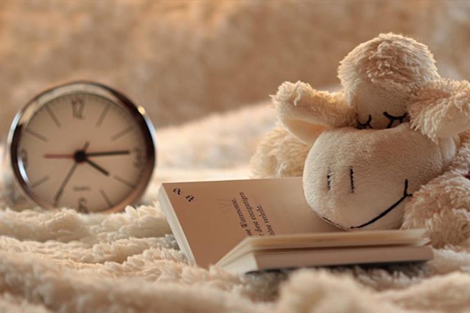 בחן את עצמך: שעון ובובת כבשה ישנה על ספר