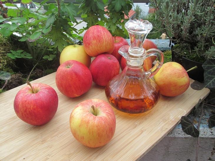 תרופות ביתיות לכלב מתגרד: תפוחים על שולחן ובקבוק של חומץ תפוחים