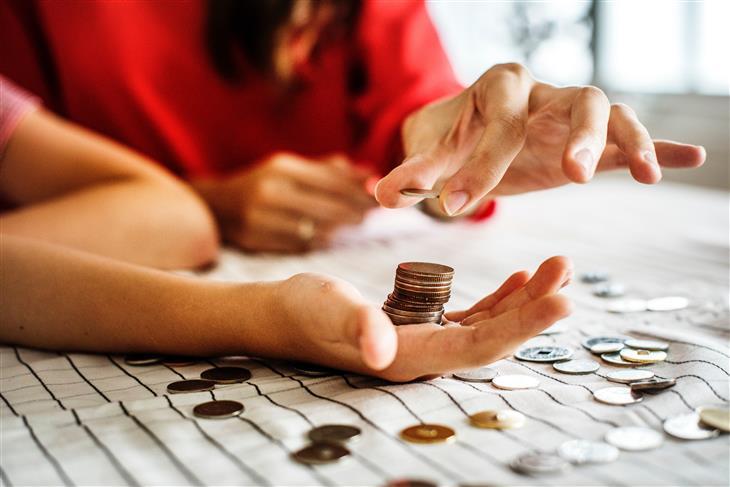 איך לחסוך בהוצאות הקבועות: אישה יוצרת מגדל של מטבעות על כף היד של בתה