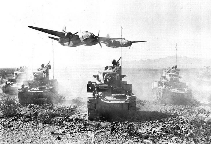 תמונות היסטוריות: טנקים אמריקאים ומעליהם שני מטוסים הטסים נמוך במהלך אימון בקליפורניה, ארצות הברית, 1942.