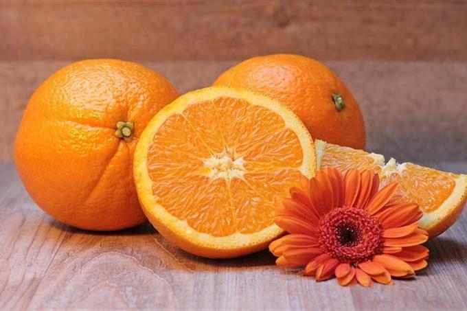 מבחן אישיות אסוציאציות ורמת נחמדות: שלושה תפוזים כשאחד מהם חתוך לחצי ולידם פרח כתום