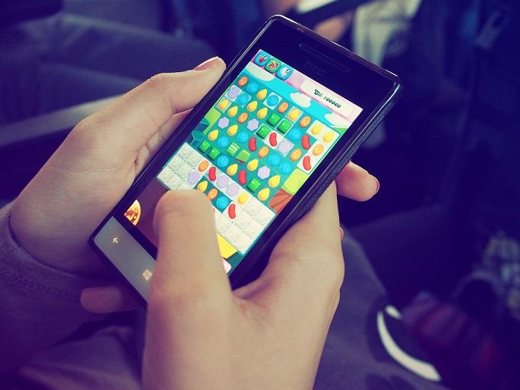 משחקים לטלפון הנייד: שתי ידיים משחקות במשחק בטלפון הנייד
