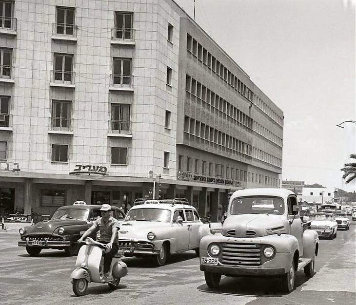 """17 תמונות ישנות של תל אביב: תנועה כלי רכב בדרך פתח תקווה (לימים דרך מנחם בגין), ברקע בית """"מעריב"""". תל אביב 1965 -1962."""