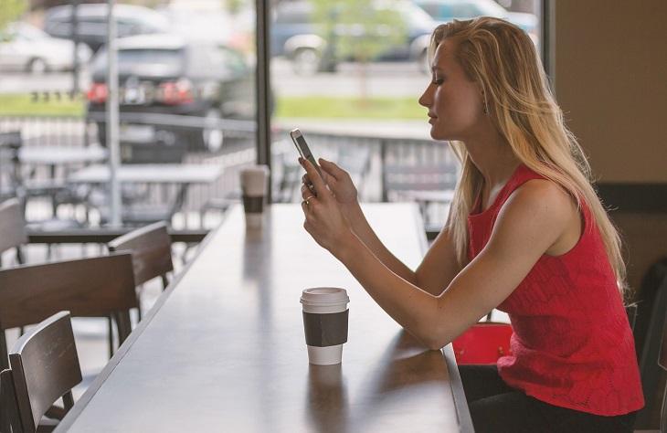 אפליקציות לשמירה על הפרטיות בטלפון הנייד: אישה מתבוננת בטלפון הנייד שלה
