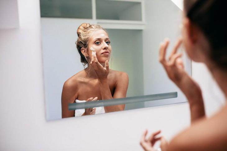טיפים לאיפור: אישה מורחת פריימר מול מראה