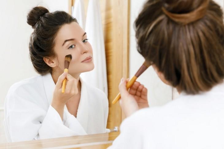 טיפים לאיפור: אישה מעבירה מברשת איפור על הלחיים שלה מול מראה