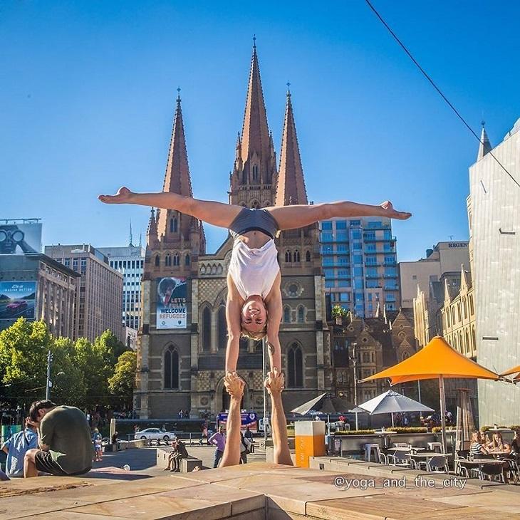 יוגה בעולם: גבר ואישה עוסקים ביוגה על רקע כיכר וכנסייה במלבורן, אוסטרליה