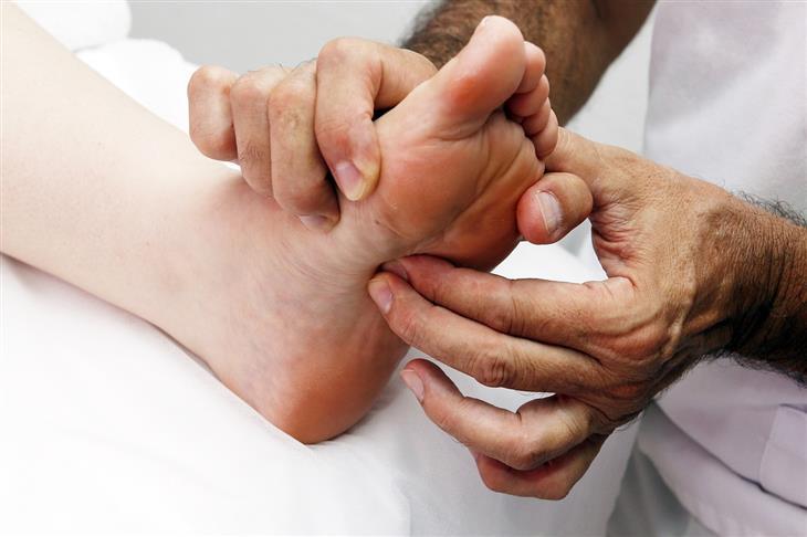 נקודות לחיצה לטיפול בבעיות בשתן ובכליות: מטפל לוחץ על נקודה בכף רגל של מטופל