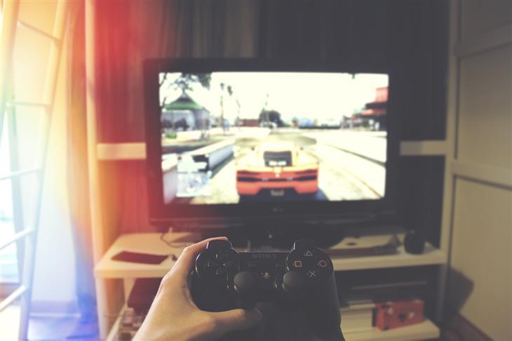 התמכרות של ילדים למשחקי מחשב: יד מחזיקה של של פלייסטישן מול טלוויזיה