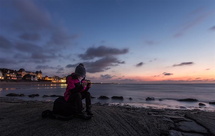 התמכרות של ילדים למשחקי מחשב: ילד משחק בנינטנדו סוויץ' בחוף ים בשעת שקיעה