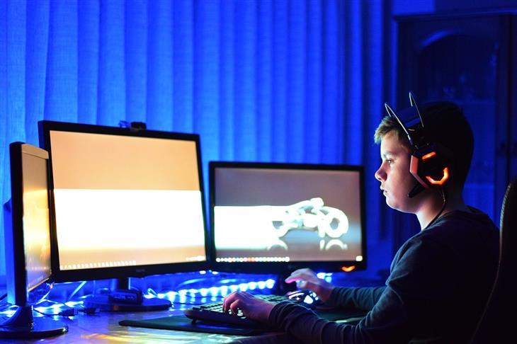התמכרות של ילדים למשחקי מחשב: ילד משחק במחשב מול שלושה מסכים