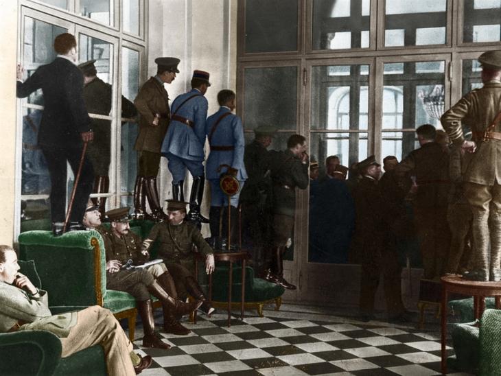 תמונות היסטוריות: אנשים עומדים על רהיטים ומנסים להביט לתוך אולם כנסים