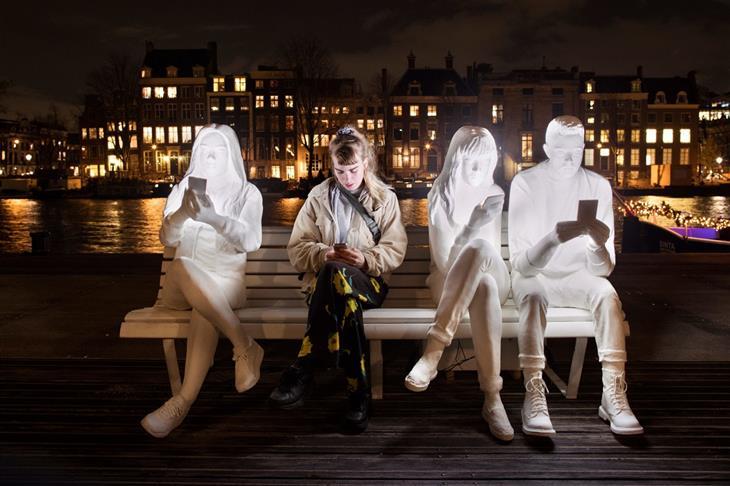 פסטיבל האור של אמסטרדם 2018: מייצג אור שך פסלים בדמות אנשים יושבים על ספסל ומתבוננים בטלפון נייד, לצד בחורה בשר ודם