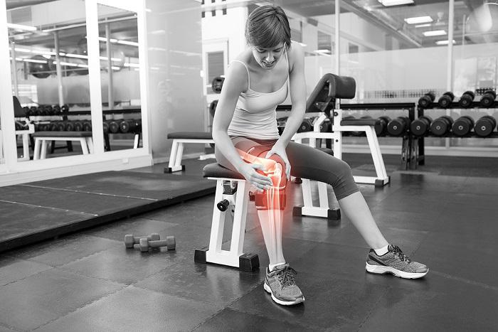 כאבי ברכיים - סיבות נפוצות ודרכי טיפול: בחורה באימון מחזיקה את הברך