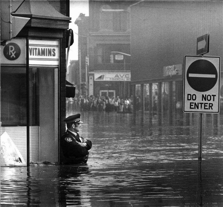 תמונות היסטוריות: שוטר עומד בתוך מים עד המותניים ברחוב מוצף