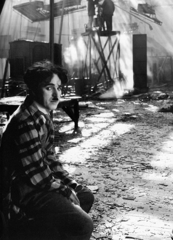 תמונות היסטוריות: צ'רלי צ'פלין מביט על המצלמה במבט עצוב כשמאחוריו סט שרוף של קרקס