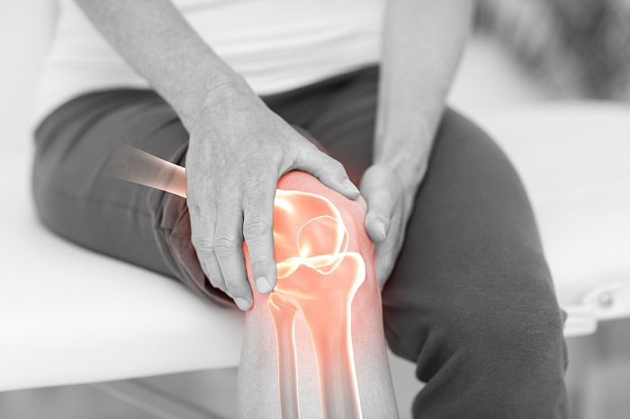 כאבי ברכיים - סיבות נפוצות ודרכי טיפול:  גבר מחזיק את הברך הכואבת