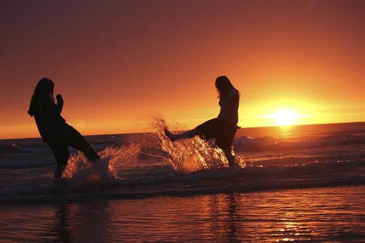 תובנות על אנשים ויחסים: נשים בשקיעה משפריצות מים עם הרגליים אחת על השנייה בים
