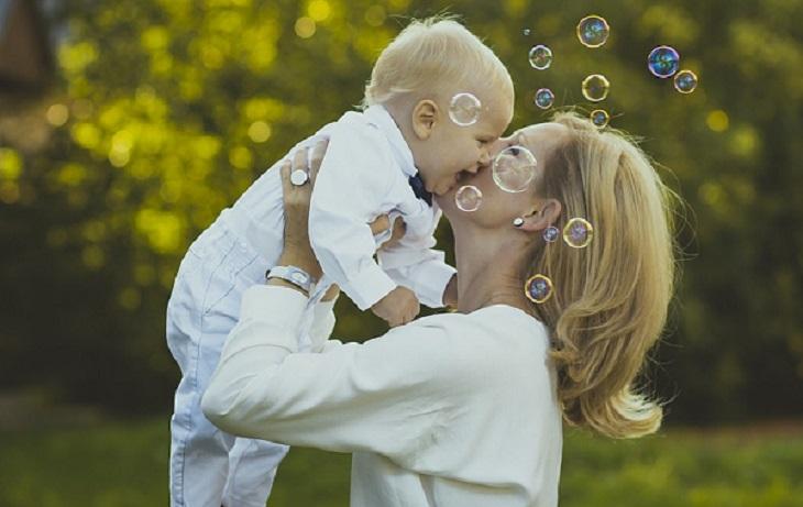 5 דרכים למניעת קנאה: אישה מניפה תינוק ומנשקת אותו