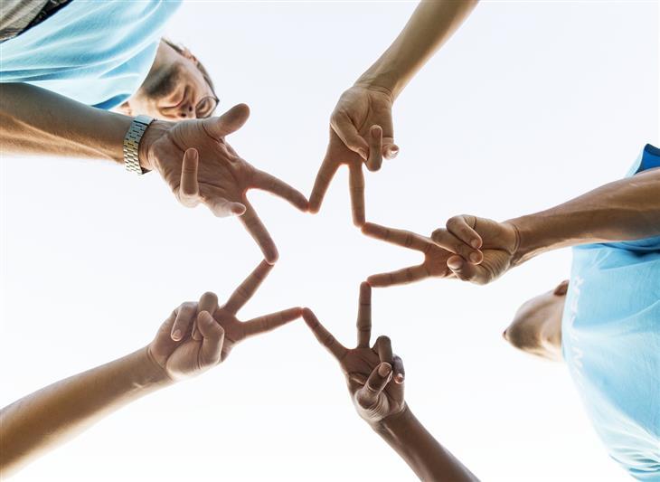 תובנות על אנשים ויחסים: אנשים מצמידים אצבעות במעגל ויוצרים צורת כוכב