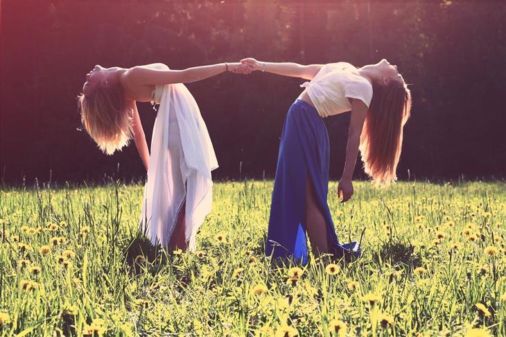 תובנות על אנשים ויחסים: שתי נשים מחזיקות ידיים ונשענות לאחור בשדה פרחוני