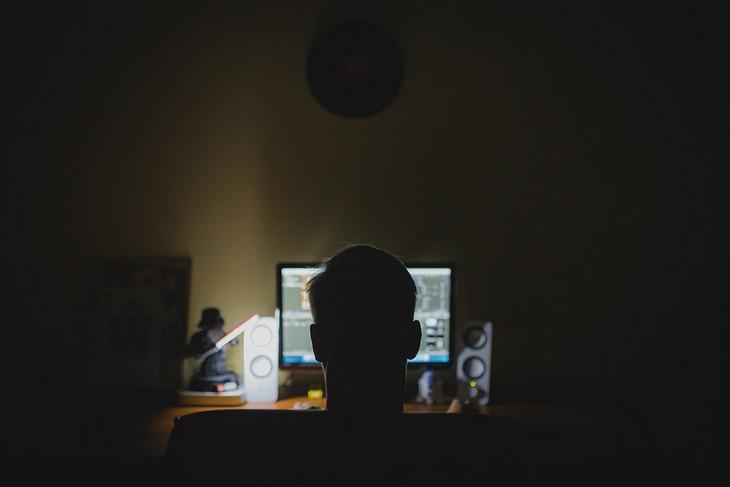הונאות אינטרנט: דמות של גבר יושבת מול מחשב נייד בחדר חשוך
