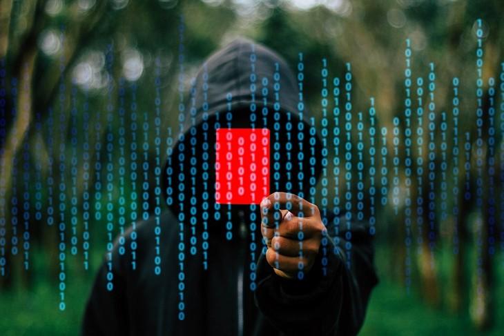 הונאות אינטרנט: גבר עם קפוצ'ון מחזיק קלף אדום מול המצלמה והתמונה מכוסה במספרים
