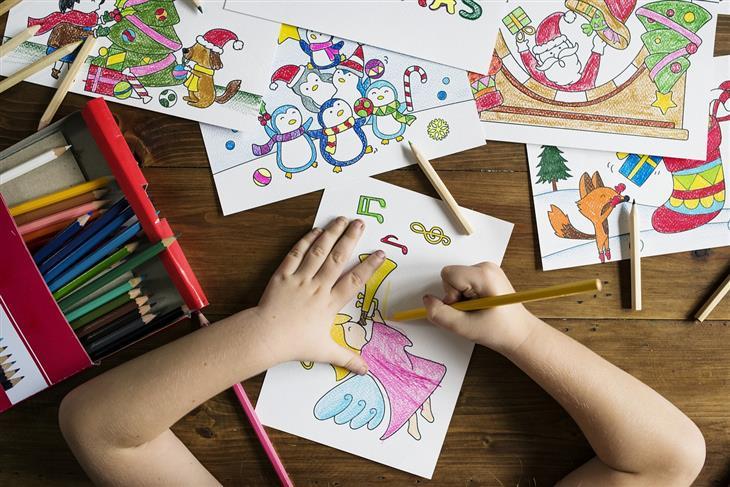 טיפים להכנת הילדים לקראת מקצועות העתיד: ידיים של ילד מצייר ושולחן מלא בציורי ילדים
