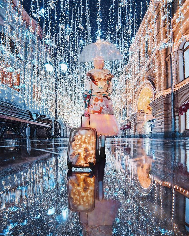 אגדה חורפית ברוסיה - מוסקבה מקושטת באורות: אישה עם מטריה ברחוב מלא בנורות