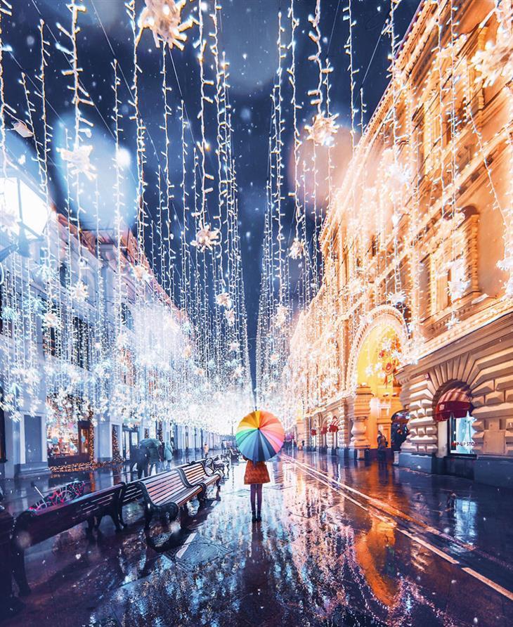 אגדה חורפית ברוסיה - מוסקבה מקושטת באורות: אישה עומדת עם מטריה ברחוב מואר