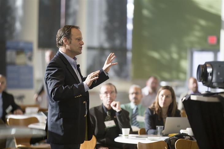 טיפים לשיפור שפת הגוף להצלחה בקריירה: איש בחליפה מדבר מול קהל עם ידיים לפניו