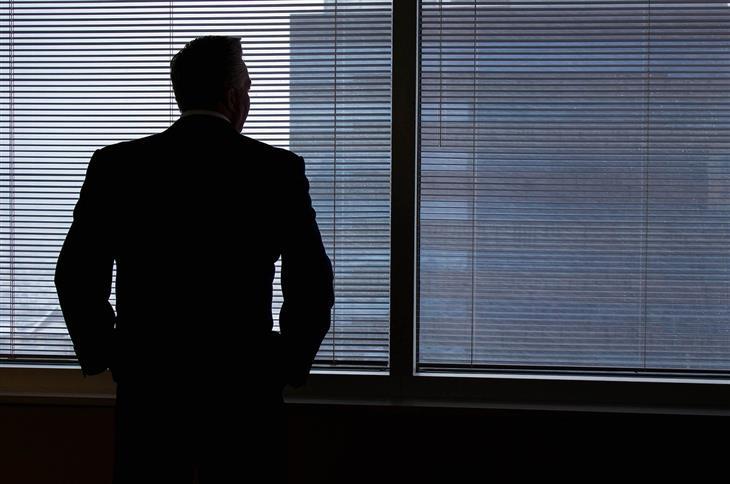 טיפים לשיפור שפת הגוף להצלחה בקריירה: איש בחליפה מסתכל מבעד לחלון
