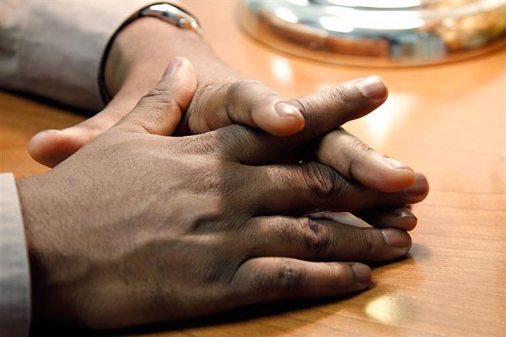 טיפים לשיפור שפת הגוף להצלחה בקריירה: איש משלב אצבעות על שולחן