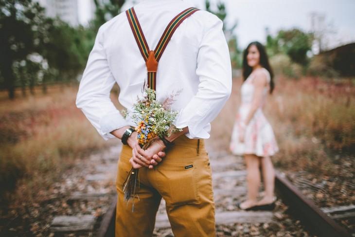 סימנים לאהבה חדשה: גבר עומד מול אישה ומחזיק מאחורי גבו זר פרחים