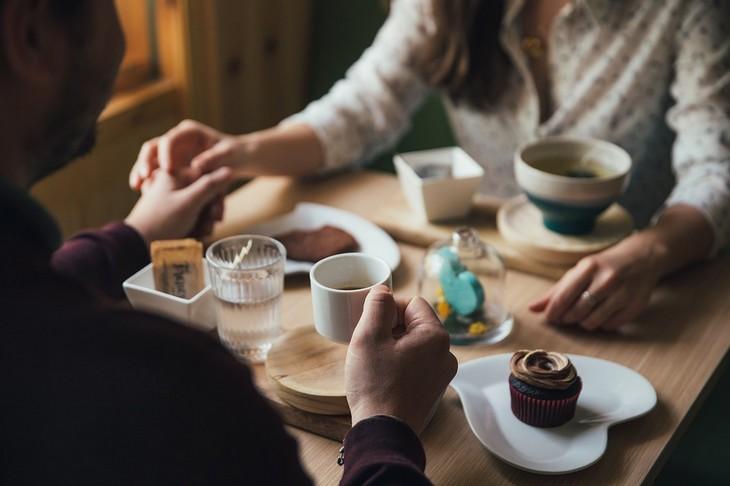 סימנים לאהבה חדשה: גבר ואישה יושבים ליד שולחן אוכל כשהם מחזיקים ידיים