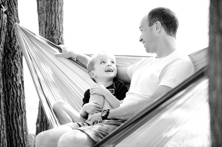 עקרונות הורות מודעת של דוקטור שפאלי טסברי: הורה וילד יושבים על ערסל ומדברים ביחד