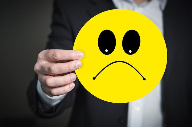 סימנים לדום נשימה בשינה: איש בחליפה מחזיק תמונה של סמיילי עצוב