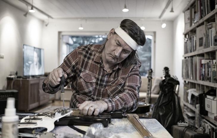 סרטוני הדרכה לתיקונים בבית: אדם עובד עם מברג לתיקון בביתו