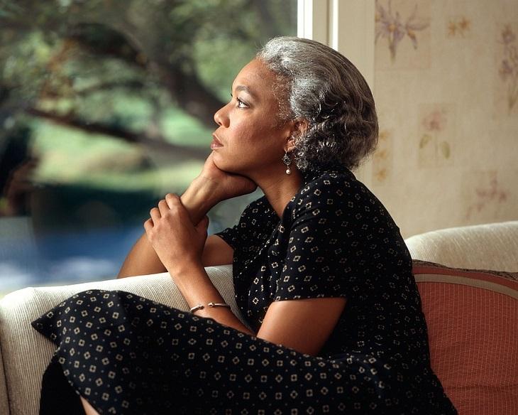 שאלות לקבל החלטות: אישה מבוגרת יושבת על הספה ומניחה את ראשה על ידה במבט חושב