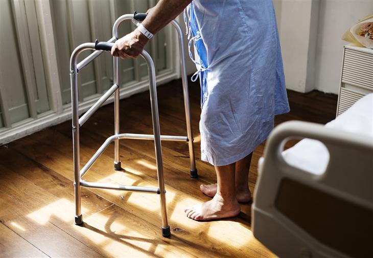 הקשר בין שינה לקויה לאיבוד שיווי משקל: אדם קשיש עם הליכון בבית חולים
